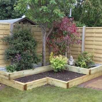 Wooden panel, concrete post in back garden fence and raised beds in Nottingham